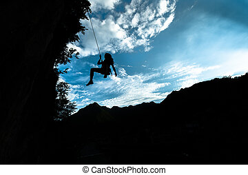 Silhouette of a girl coming down from the rope after climbing