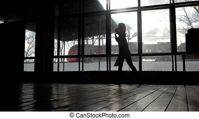 Silhouette of a girl dancing in front of a window