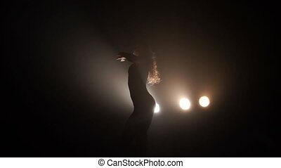 Silhouette of a girl dancing on the background lights