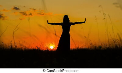 Shot of a young woman silhouette doing yoga at sunset. Shot in RAW format.