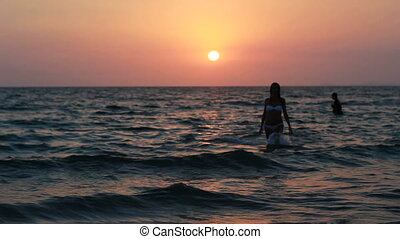 Silhouette of a girl in the water at sunset.