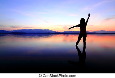 Silhouette of a girl in the water at sunset