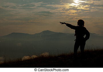 silhouette of a girl on a background of clouds sky in the mountains