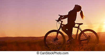 Silhouette of a girl on a bicycle in the sunset.