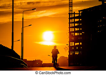 Silhouette of a girl on a bicycle on a bridge during sunset