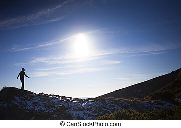 Silhouette of a girl on top of a mountain.