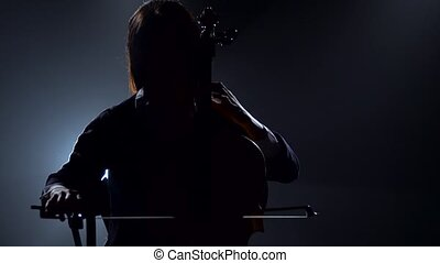 Silhouette of a girl playing the cello in a night studio. Black smoke background