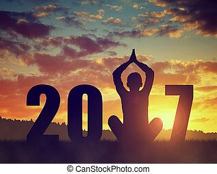 Silhouette of a girl practicing yoga in the New Year