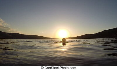Silhouette of a girl swimming in the sea during beautiful sunset