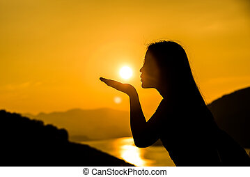 Silhouette of a girl with the sun in her hands