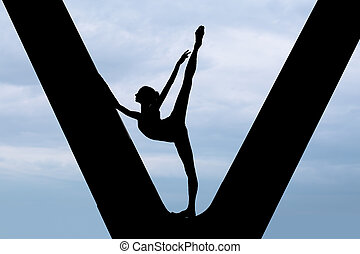 Silhouette of a graceful ballerina in a black bathing suit...