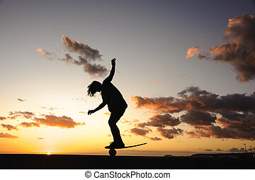 Silhouette of a guy standing on a balance board