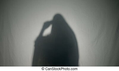 Silhouette of a Halloween possessed woman ghost dialing a...