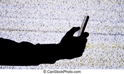 Silhouette of a Hand Holding a Smartphone on TV Screen Background with White Static Noise. Male fingers use a touchscreen of mobile phone. TV interference, no signal display. Phone addiction concept, no connection, hopelessness