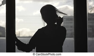Silhouette of a happy girl dancing in front of a window