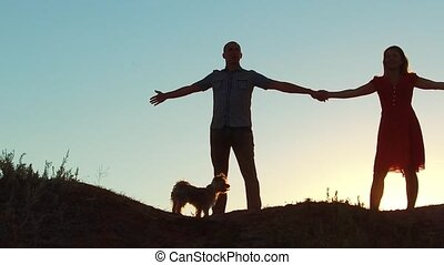 silhouette of a happy young married couple and dog slow...