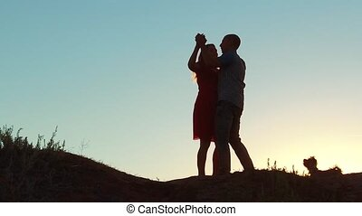 silhouette of a happy young married couple and dog slow dancing outside at sunset. slow motion video. man and girl dancing salsa at sunset. Unidentifiable Silhouette of dancing couple love friendship lifestyle and dog concept family video