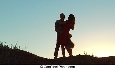 silhouette of a happy young married couple and dog slow dancing outside at sunset. slow motion video. man and girl dancing salsa at sunset. Unidentifiable Silhouette of dancing couple love friendship and dog concept family video lifestyle