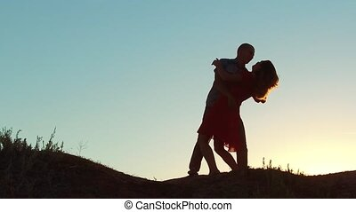 silhouette of a happy young married couple and dog slow dancing outside at sunset. slow motion video. man and girl dancing salsa at sunset. Unidentifiable lifestyle Silhouette of dancing couple love friendship and dog concept family video