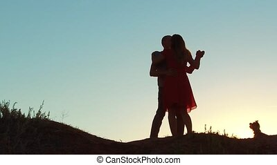 silhouette of a happy young married couple and dog slow dancing outside at sunset. slow motion video. man and girl dancing salsa at sunset. Unidentifiable Silhouette of dancing couple love lifestyle friendship and dog concept family video