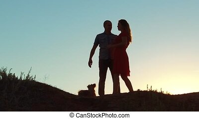 silhouette of a happy young married couple and dog slow dancing outside at sunset. slow motion video. man and girl dancing salsa at sunset. Unidentifiable Silhouette of dancing lifestyle couple love friendship and dog concept family video
