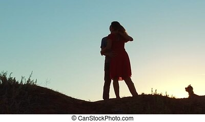silhouette of a happy young married couple and dog slow dancing outside at sunset. slow motion video. man and girl dancing salsa at sunset. Unidentifiable Silhouette of dancing couple lifestyle love friendship and dog concept family video