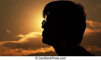 Silhouette of a head of the man against the sun