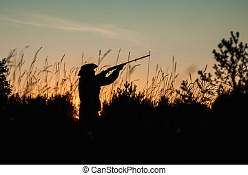 Silhouette of a hunter in a cowboy hat with a gun in his hands on a background of a beautiful sunset. The hunting period, the fall season is open, the search for prey.