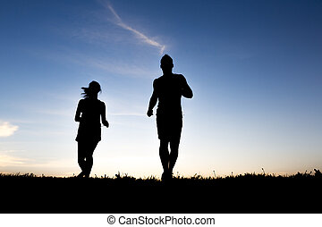 silhouette of a jogger couple in sunrise - A silhouette of a...