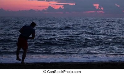 Silhouette of a kickboxer workout during sunset on the beach.