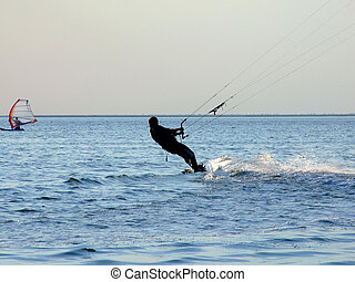 Silhouette of a kite-surf on waves of a gulf 1