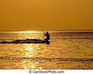 Silhouette of a kite-surf on waves of a gulf on a sunset 1