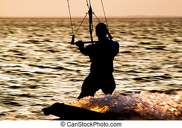 Silhouette of a kitesurfer on a gulf