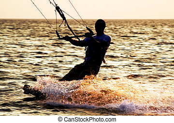 Silhouette of a kitesurfer on a waves