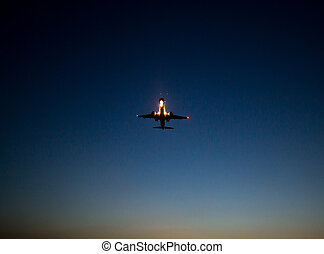 Silhouette of a landing aircraft at sunset