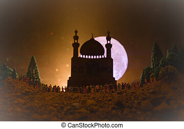 Silhouette of a large crowd of people in forest at night standing against a blurred mosque building with toned light beams on foggy background. Ramadan Kareem background.