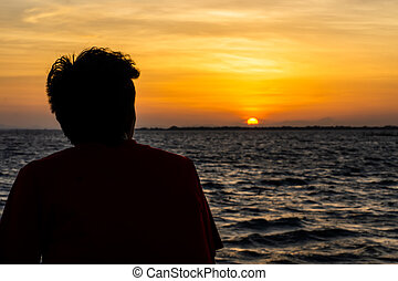 Silhouette of a lonely man at sunset