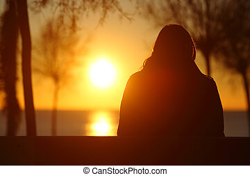 Silhouette of a lonely woman watching sunset in winter