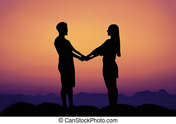 Silhouette of a love couple at sunset as symbol for wedding