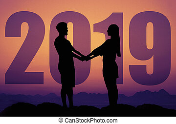 Silhouette of a love couple at sunset with new year 2019
