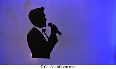 Silhouette of a male classical singer singing with a microphone in the studio,