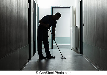 Male Janitor Cleaning Corridor