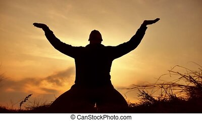 silhouette of a male monk engaged in meditation at sunset...