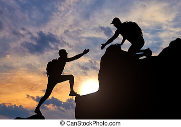 Silhouette of a male mountaineer working in a team with a partner, giving him a helping hand