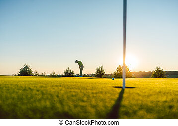 Silhouette of a male player hitting a long shot on the golf course
