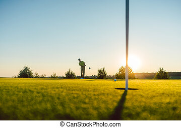 Silhouette of a male player hitting a long shot on the putting g
