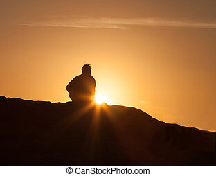 Silhouette of a man alone at sunset