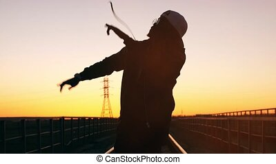 Silhouette of a man dancing at sunset