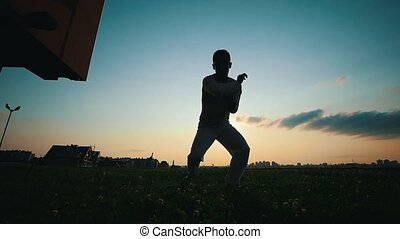 Silhouette of a man dancing capoeira at sunset, summer evening
