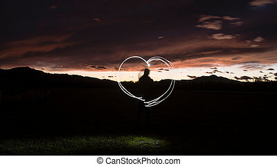 Silhouette of a man draws a heart shape with a flashlight through the air
